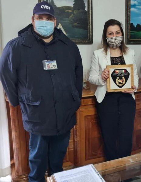 Il presidente Patellaro dell'associazione O.V. D.T.S. dona all'assessore Paola Naimi il loro stemma.